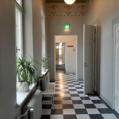 lång korridor med svartvitrutigt golv, vita spegeldörrar på gläntoch fönstersmygar med palmer i kruka