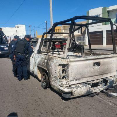 Poliisit tutkivat palanutta autoa.