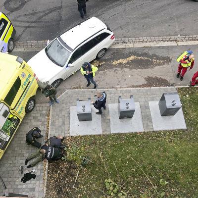 Poliisi ottaa maassa makaavan miehen kiinni.