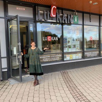 Jenny Paajes står och håller upp glasdörren till Luckan i Kyrkslätt. I fönstret syns Luckans logo, och Jenny är klädd i en grön klänning. Hon ler, och ser in i kameran.