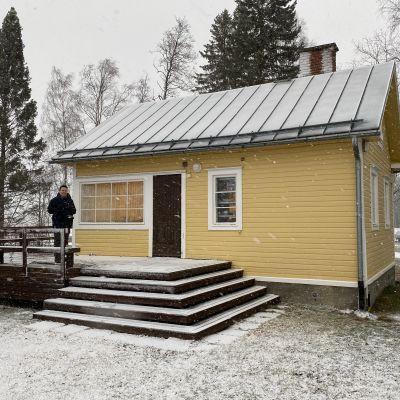 Man står på trappan till litet hus i snöstorm.