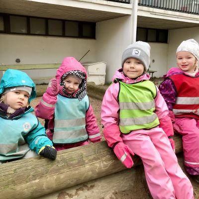 Fyra dagisbarn i regnkläder på sandlådskant.