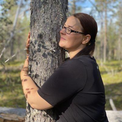 Metsäjoogaohjaaja Minna Kataja halaamassa mäntyä.