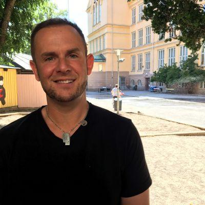 Rektor Mikael Lindberg står på sin skolgård. Han har svart t-skjorta och det leker barn i bakgrunden.