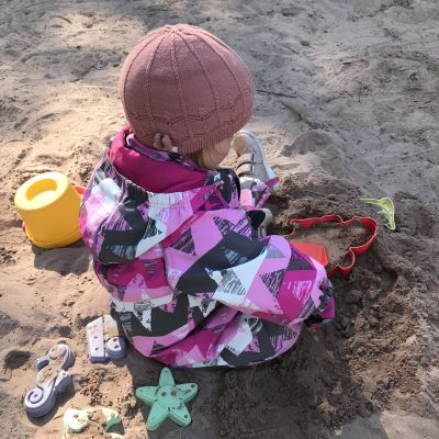Ett litet barn i halare och mössa leker i en sandlåda.