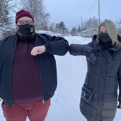 Kainuun keskustan toiminnanjohtaja Minna Peittola ja Kajaanin vasemmiston puheenjohtaja Miikka Kortelainen tekevät kyynärpäillä koronatervehdyksen.