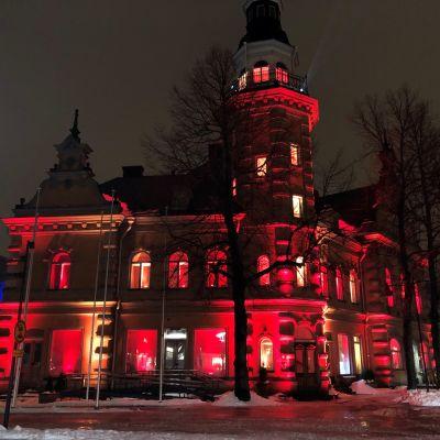 Rauman kaupungintalon vanha osa punaiseksi valaistuna.