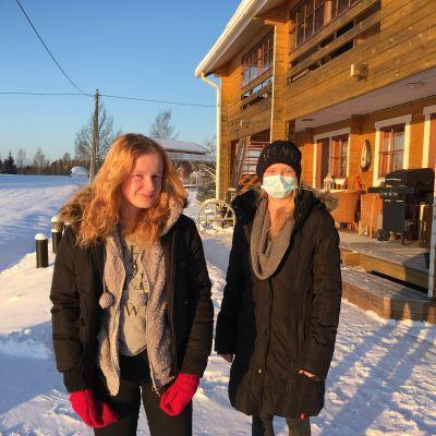 Tytär ja äiti seisovat talonsa edessä auringonpaisteessa talvella