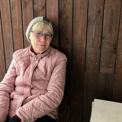 Tove Fagerholm i rosa jacka sitter på en bänk. I bakgrunden snö.