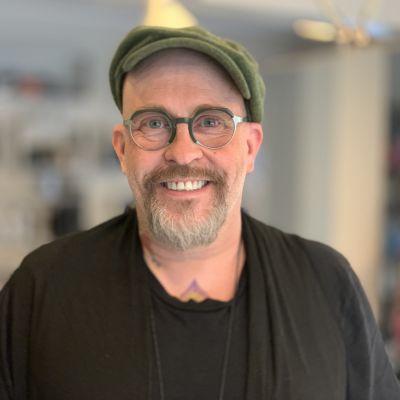 En man med skärmmössa, glasögon och skägg tittar leende in i kameran.