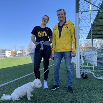 Mies ja nainen poseeraavat kameralle jalkapallokentän vieressä