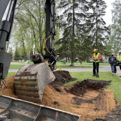 Kaivinkone kaivaa kuoppaa puistossa, kolme ihmistä katsoo vierestä.