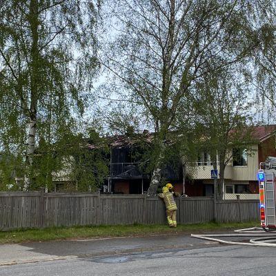 Ett tvåvåningsradhus som brunnit, av fyra lägenheter är de två mittersta förkolnade. På gatan står två brandmän och diskuterar. Bakändan av en brandbil syns.