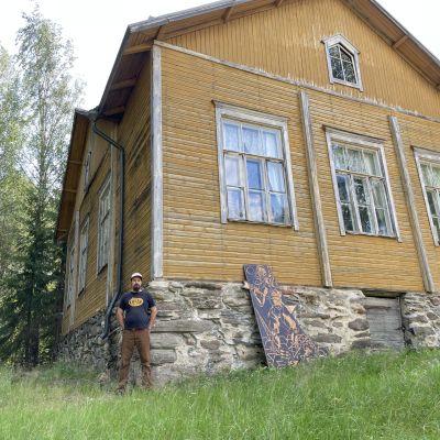 Joona Hamm seisoo kaksikerroksisen hirsisen kansakoulun seinän vieressä.