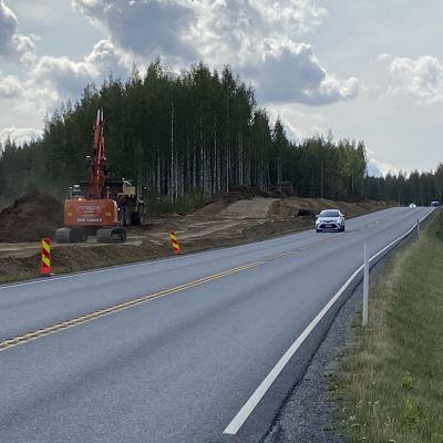 Kaivuri uuden tienpohjan päällä valtatien vieressä, henkilöauto ajaa tiellä
