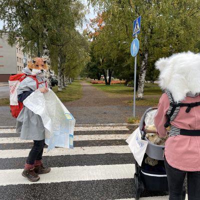 Kettuhahmo ja jääkarhuhahmo ylittävät suojatietä.
