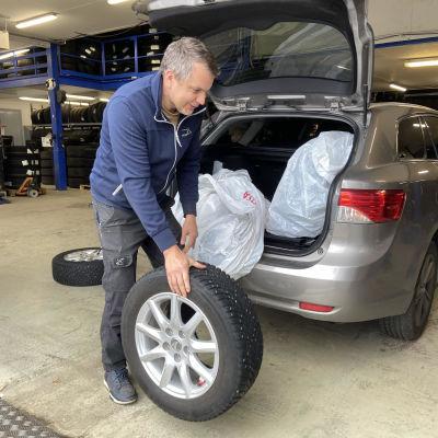 Joensuulaisen JV-Renkaan yrittäjä Ville Lainpelto ottaa rengasta pois auton takakontista.