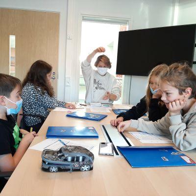 Fyra elever och en lärare i rum.