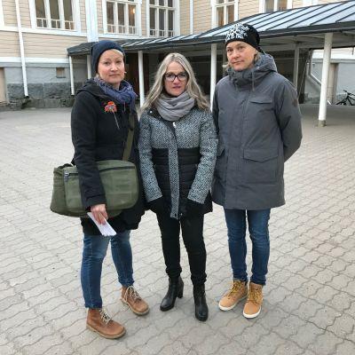 Kolme naista seisoo koulun pihalla