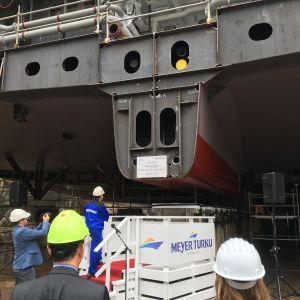 Flera personer följer med kölsträckningen av kryssningsfartyg.