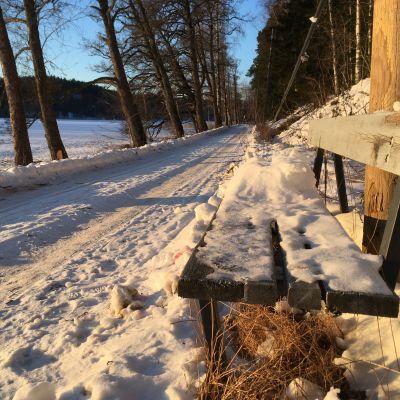 En vintrig väg och en bänk.