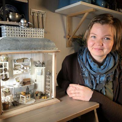 Salla Heikkilä med en lykta som är inredd med miniatyrmöbler