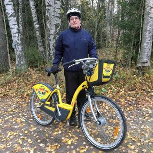 Antti Oramo seisoo syksyisessä maisemassa kapunkipyörän kanssa.