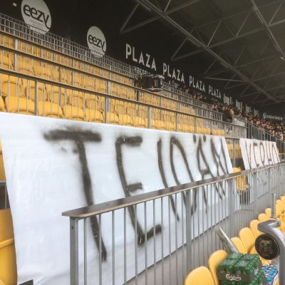 """Seinäjoen jalkapallostadionin kannattajapäädyssä kyltti, jossa lukee protestina """"Teidän kerho""""."""