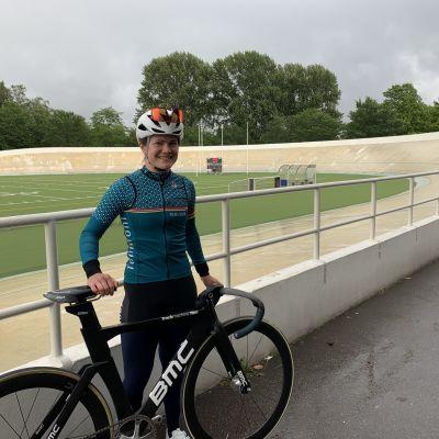 Ida Sten står vid Velodromen i Helsingfors med sin svarta bancykel. På sig har hon en vit hjälm, ett par röda solglasögon och sin turkosa tävlingsrock.