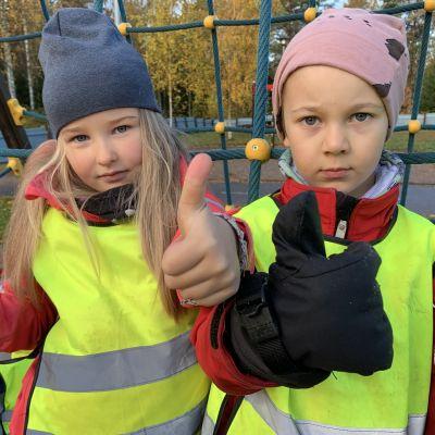 Alma och John deltar i försöket med tvåårig förskola. Här står de framför en klätterställning och visar tummen upp för sin förskola, Knattebo i Malax.