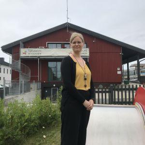 Kvinna poserar framför byggnad