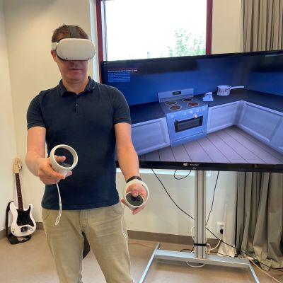 Kajaanin ammattikorkeakoulun pelituottaja Kyösti Koskela pelaa pakopeli Mysteeriä VR-lasit päässään. Kädessään hänellä on ohjaimet, joilla voi esimerkiksi noukkia lattialta roskia.