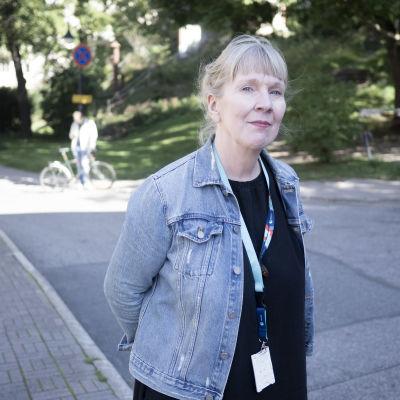 Kvinna med blont hår och jeansrock ute i solskenet i park.