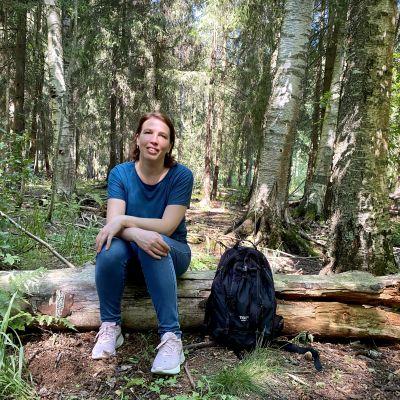 Nina Karisalo istuu puun rungolla Matokallion metsässä.