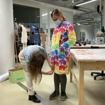Opettaja Iida Silvennoinen asettelee elefanttikuvioista takkia, joka on muoti- ja puvustusalan opiskelija Piia Selinkosken päällä.