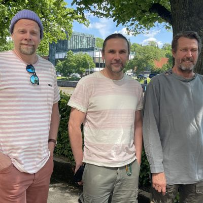 Näyttelijät Martti Suosalo ja Ville Myllyrinne poseeraavat ohjaaja JP Siili keskellään Turun Aurajokirannassa