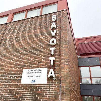 Bild på tegelhusfasad. På en skylt står det Kotka Svenska Barnträdgård. Bokstäver bildar ordet Savotta.