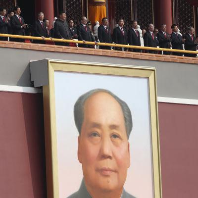 Kinesiska ledare följer med en militärparad vid Tiananmen (Himmelska fridens port) i Peking under Folkrepublikens 70-årsjubileum i oktober 2019. Ledarna är fotograferade ovanför det enorma Mao-porträttet vid porten.