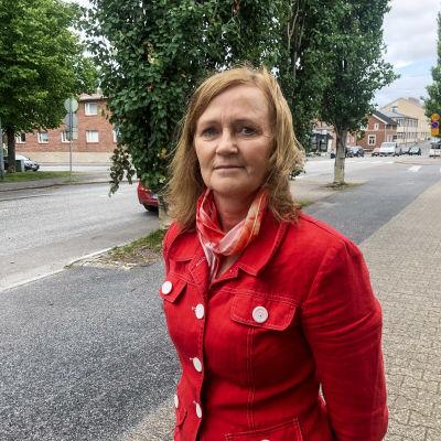 Kvinna i röd jacka står på trottoar. Bilar och träd i bakgrunden.