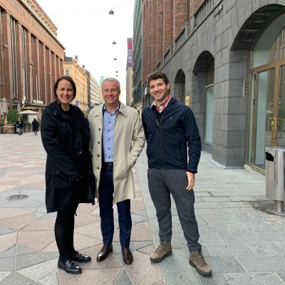 Från vänster står Veronika, Marcus och Ted mellan Akademiska Bokhandeln och Stockmanns varuhus i Helsingfors, leende mot kameran och med ytterkläder på.