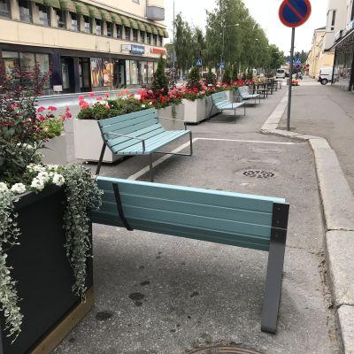 Mikkelin kävelykatukokeilun kukkaistutuksia ja penkkejä. Kuvassa isojen kukka-astioiden kukat ovat pinkkejä ja punaisia.