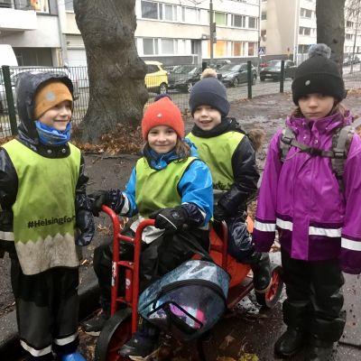 Fyra barn i dagisåldern i regnväder.