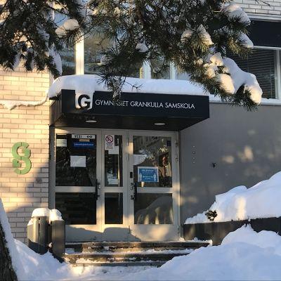 Gymnasiet Grankulla Samskola, fasaddörr med snödrivor i vintersol.