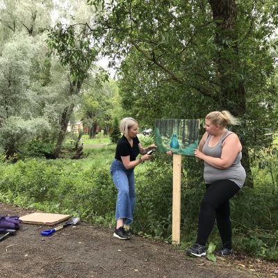 Jasmin Lier ja Minna Heikkilä kiinnittävät valokuvateosta puiseen telineeseen Pappilanpellon lintupolun varressa.