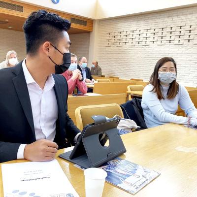 Man och kvinna med vietnamesiskt ursprung i fullmäktigesalen