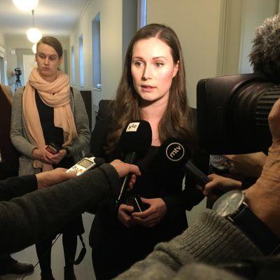 Sanna Marin svarar på journalisters frågor i riksdagen.
