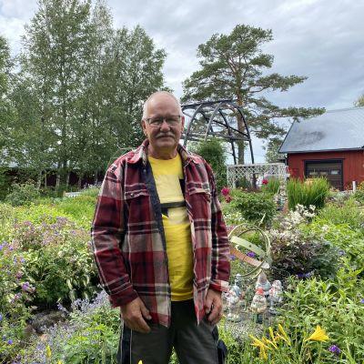 Krister Stenback står framför en blommande trädgård.