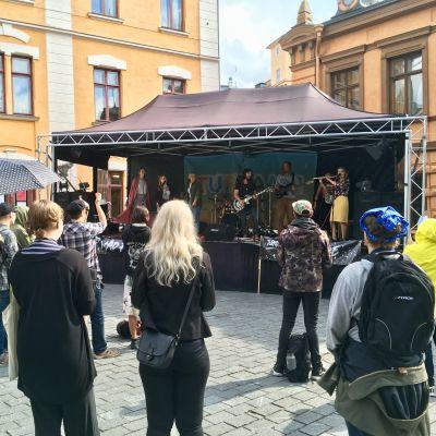 Publiken lyssnar på ett band som spelar på Mad Pride på Gamla Stortorget i Åbo.
