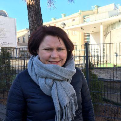 Kuvassa johtava diakoniatyöntekijä Camilla Honkala seisoo seurakuntakeskuksen pihalla.