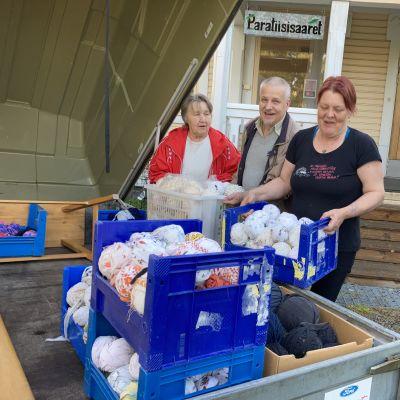 Paratiisisaarten vapaaehtoiset pakkaavat tavaraa peräkärryyn.